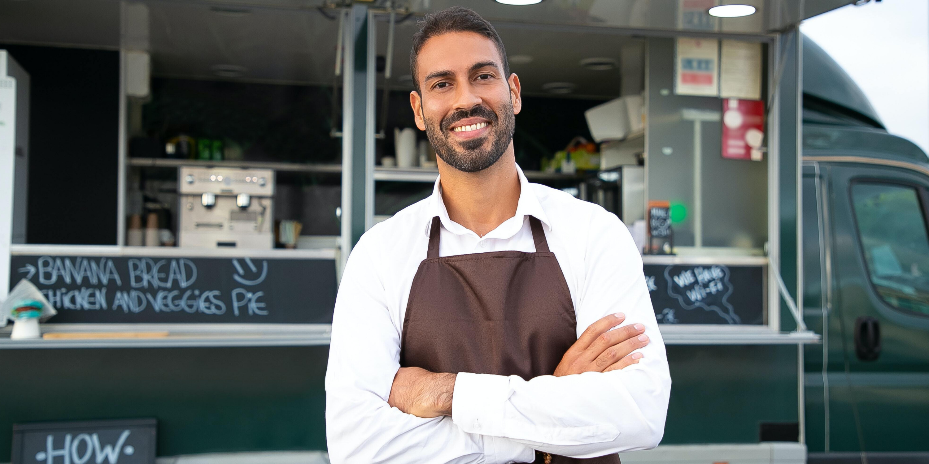 Small business owner smiling and wearing a brown apron standing in front of his food truck